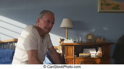Senior man sitting on bed at home