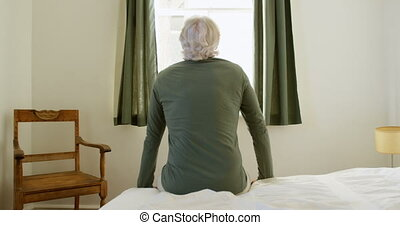 Senior man sitting on bed in bedroom at home 4k