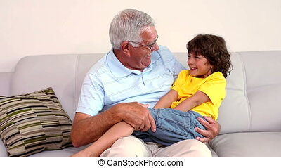 Senior man sitting on couch with his grandson at home in the...