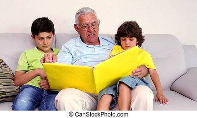 Senior man sitting on couch with his grandsons looking at...