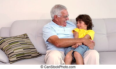 Senior man sitting on couch with hi