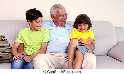 Senior man sitting on couch with his grandsons at home in...