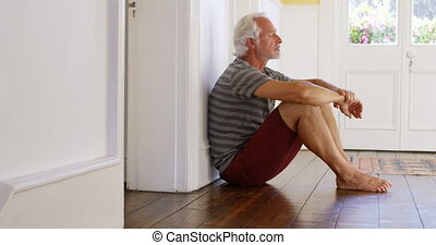 Senior man sitting on floor at home 4k