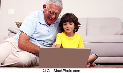 Senior man sitting on floor with his grandson using laptop...
