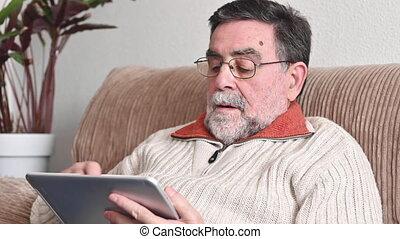 Senior man sitting on sofa using digital tablet in living room.