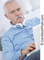 senior man sitting on sofa with headphones and using laptop