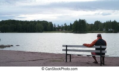 Senior Man Sitting On The Bench By The Lake - Portrait of...