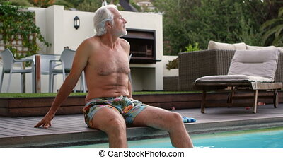 Senior man sitting on the edge of swimming pool 4k - Active...