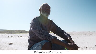 Senior man sitting on the sand at the beach