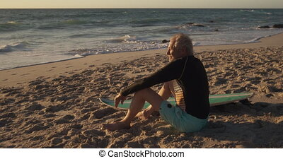Senior man sitting on the sand at the beach