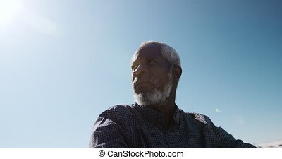 Senior man sitting on the sand