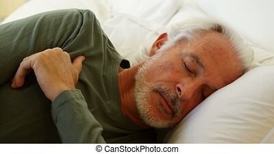 Senior man sleeping on bed in bedroom at home 4k