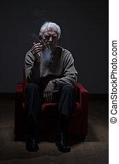 Senior man smoking cigarette - Senior man sitting in an...