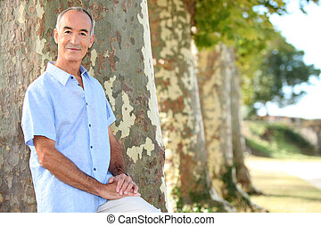 Senior man standing by a row of trees