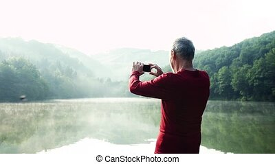 Senior man standing by the lake outdoor in foggy morning in...