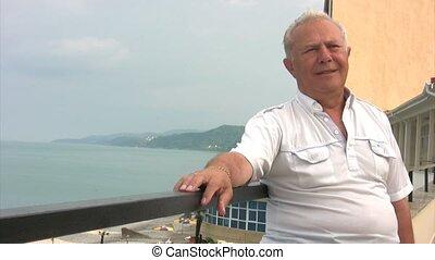 senior man standing near balustrade, sea in background