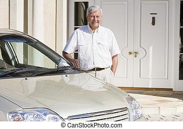 Senior man standing next to new car