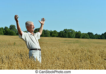 Senior man standing on wheat field with cloudy sky on ...