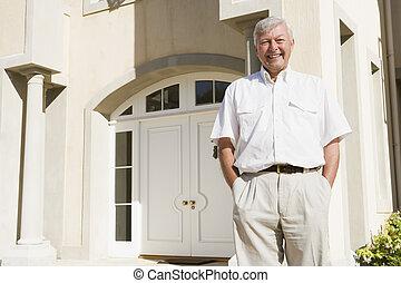 Senior man standing outside house