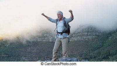 Senior man standing with arms up on a rock at countryside 4k