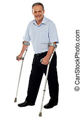 Senior man standing with the help of crutches