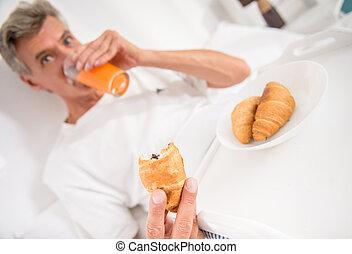 Senior man - Happy senior man is having breakfast in bed.