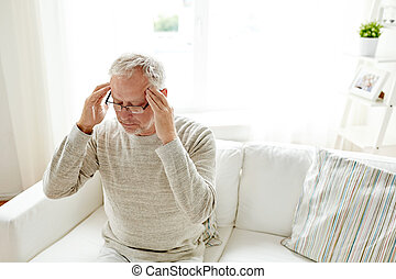 senior man suffering from headache at home