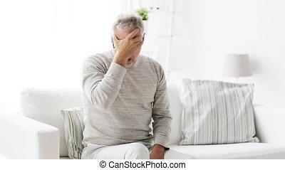 senior man suffering from headache at home 105 - health...