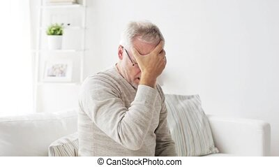senior man suffering from headache at home - health care,...