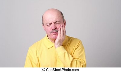Senior man suffering with terrible toothache. Problems with...