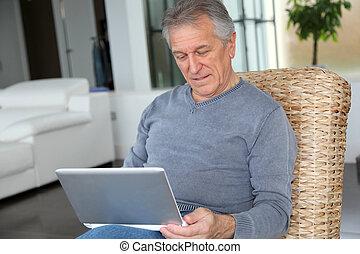 Senior man surfing on internet at home