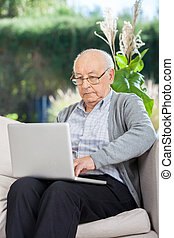 Senior Man Surfing On Laptop