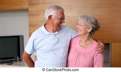 Senior man surpising partner with flowers at home in the...