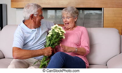 Senior man surprising partner with flowers on the couch
