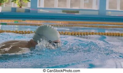 Senior man swimming in an indoor swimming pool. Active...