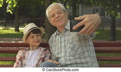 Senior man takes selfie with his grandson