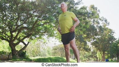 Senior man taking a break from running in the park