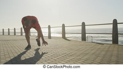 Senior man taking a break from running on the promenade