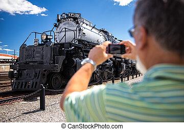 Senior man taking a photo of Union Pacific Big Boy Steam Locomotive X4012 in Scranton, PA the Union Pacific Big Boy Steam Locomotive X4012 in Scranton, PA