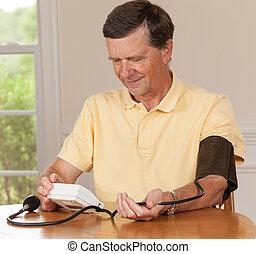 Senior caucasian retired male taking blood pressure at home