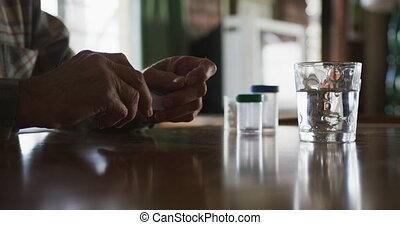 Senior man taking medical drugs at home