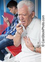 Senior man taking nitroglycerin - Senior man with chest pain...