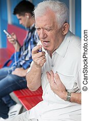 Senior man taking nitroglycerin - Senior man with chest pain...