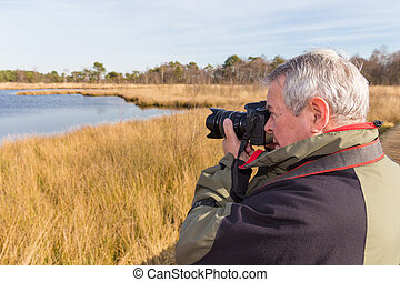 Senior man taking photos in a nature reserve