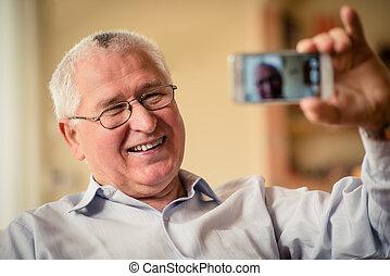 Senior man taking selfie