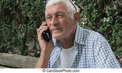 senior man talking at mobile phone - portrait of a senior...