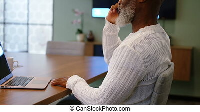 Senior man talking on mobile phone while using laptop 4k -...