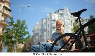 Senior man talking on phone and noting something down
