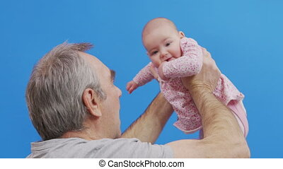 Senior man talking to his baby granddauther, holding her in the air, close up, side view. Isolated on blue background