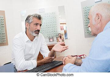 senior man talking with optician